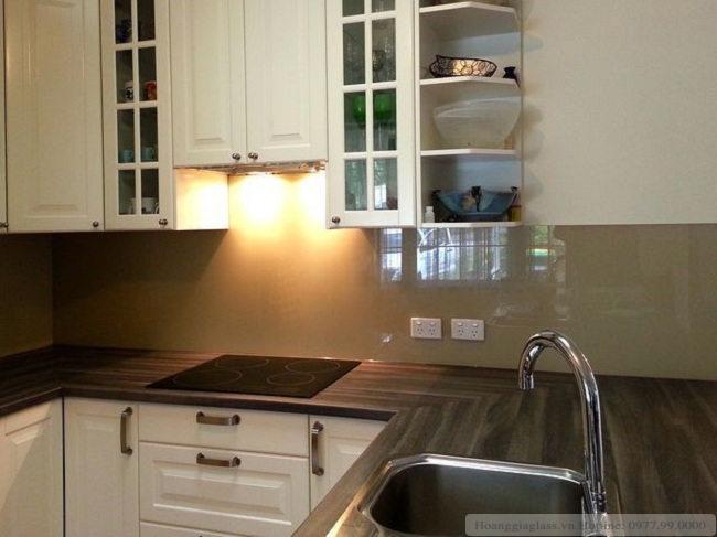 Kính ốp bếp màu vàng sữa với căn bếp hiện đại
