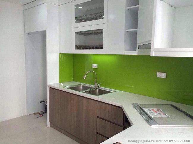 Kính ốp bếp màu xanh non kết hợp với tủ bếp màu trắng
